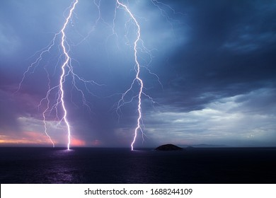 Double lightning strike over the ocean at sunset