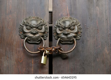 double lion knobs and lock on an old wooden gate