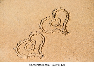 Double Love hearts impression on the sand background texture