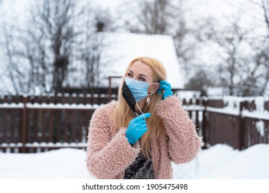 double mask. a young woman puts on the first mask with her left hand behind her ear and holds the second mask with her right hand. hands in medical gloves