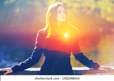 Double multiply exposure portrait of a dreamy cute woman standing outdoors, combined photograph of nature sun light, sunrise or sunset. Deep breath stress free, mind power inner voice life zen concept