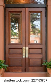 Double Natural Wood Front Doors with Windows in Brownstone with Small Potted Plants