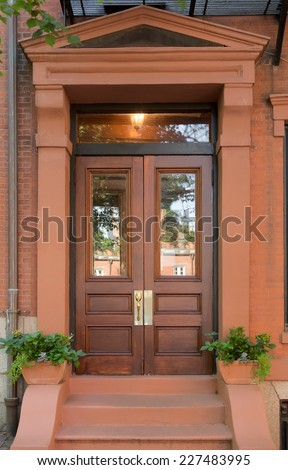 wood front door with windows craftsman double natural wood front doors with windows in brownstone portico small potted plants and steps stock photo edit now