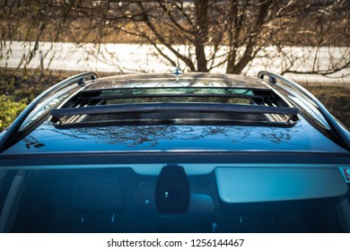 Double panoramic glazed dach open sunroof outside view. Tilted, open hatch - luxurious modern car isolated photo session in a parking lot. Close up photo, detailed.