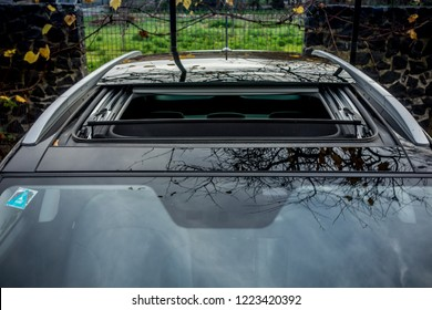 Double panoramic sunroof hatch mounted on luxurious SUV. Wind deflector with half sliding sunroof. Aerial view of wonderfull effect of open sky roof.