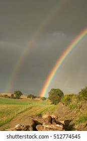 Double rainbow by a farm road