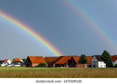 A double rainbow meteorological phenomenon seen in the blue sky after a rain shower drops down over the grass and traditional german countryside barn houses of the village of Dassensen in Lower Saxony