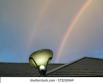 double rainbow on dark sky over roof after rain fall