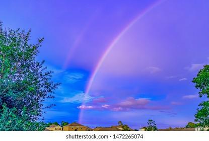 double rainbow over small houses