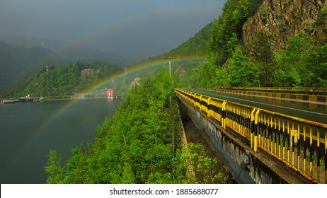 Double rainbow and rain over a bridge and lake in a summer day.