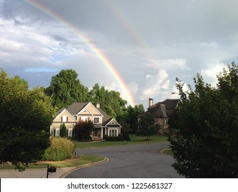 Double rainbow as seen from suburban Atlanta after a storm with clouds in the background