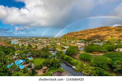 double rainbow at sunrise over tropical hawaiian island residential marina