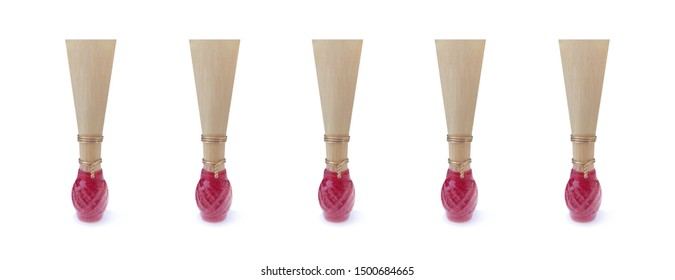 Double reed for bassoon with red thread on a wide white background. Five mouthpieces for wind musical instruments. With a slight shadow.
