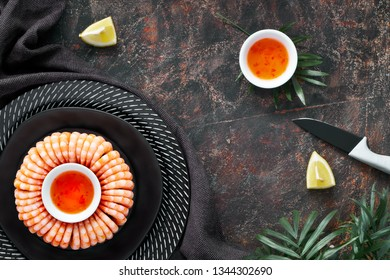 Double ring of tasty prawns served on a dark plate with lemons and sweet chili sauce, flat lay on dark textured background
