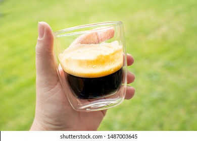 Double shot of espresso coffee in a glass double walled coffee cup. Outdoor beverage shallow depth of field with green grassy background. Delicious crema clings to glass.