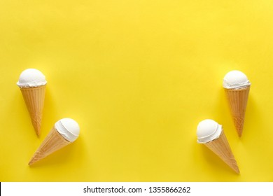 Double side border of vanilla ice cream cones on a colorful yellow background with central copy space for summer themed concepts