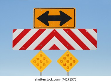 double sided arrow and reflective warning signs at a T junction on a road