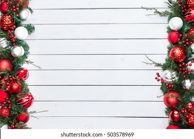 Double sided festive red and silver baubles in a Christmas border with fresh foliage and berries over rustic white stained wood with copy space