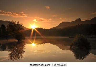 double sunrise on a peaceful lake