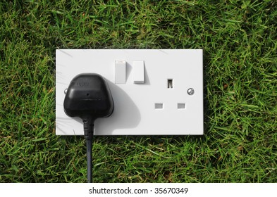 A double three pinned electrical socket with a black plug set in one unit. Set on green grass representing green energy/power.