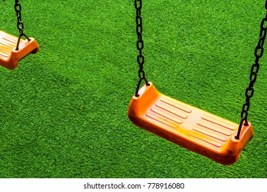 Double vivid orange color Swing seat on the artificial grass school yard
