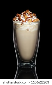 Double walled glass with coffee cocktail decorated with whipped cream and nuts isolated on black