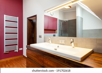 Double washbasin on wooden counter in bathroom