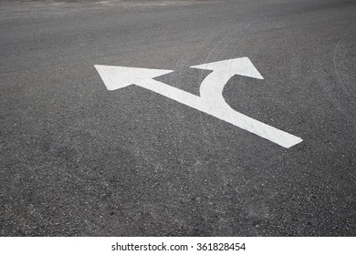 Double white arrow design in worn asphalt