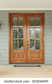 Double wooden doors to a green home. The doors have windows, and are flanked by twin light fixtures. Also seen is a doormat, and a wooden porch.