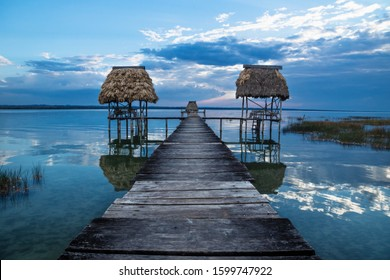 Double wooden old dock during sunset with reflexions at lake Itza, El Remate, Peten, Guatemala