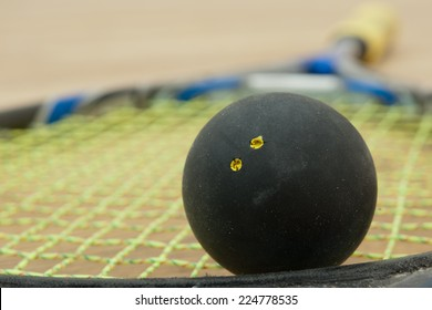 Double yellow dot official black squash ball on a yellow stringed racket in squash court