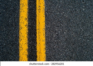 Double yellow line on black asphalt road.