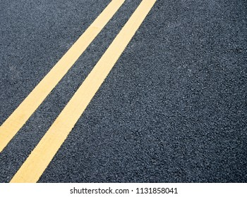 Double yellow lines on asphalt road.