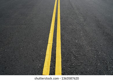 double yellow lines on new paved asphalt road surface