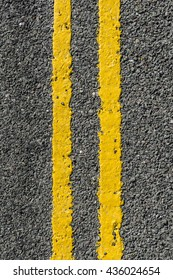 Double yellow lines painted on a loose tarmac road.