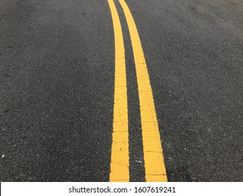 Double Yellow Lines - Yellow Traffic Lines Painted on Asphalt Surface to Divide Raod