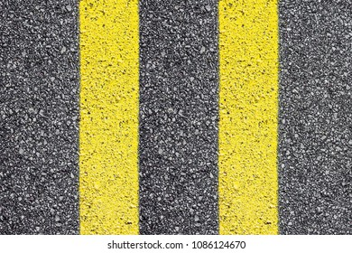 Double yellow paint line on asphalt.