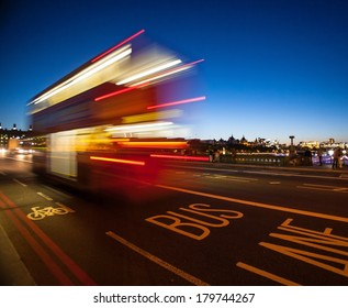 Double-Decker bus crossing Westminster Bridge at night in London, England