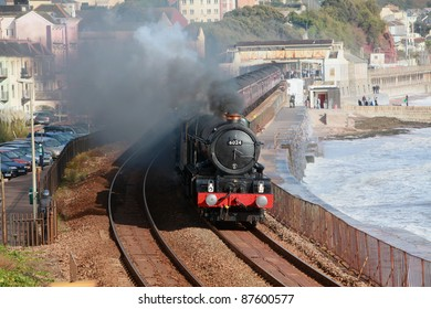 "A ""doubleheader"" locomotive leaves Dawlish station on the famous Brunel line on the south Devon coast taking steam enthusiasts on a nostalgic journey to Plymouth"