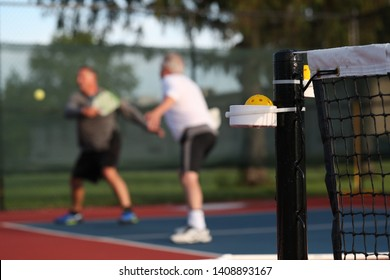A doubles pickleball team is at the net attempting to win a point.