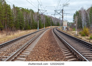 Double-track, electrified railway turns right & narrows on the horizon