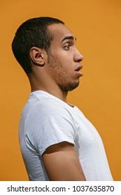 Doubt concept. Doubtful Afro-American is looking frightenedly. Young emotional man. Human emotions, facial expression concept. Profile . Studio. Isolated on trendy orange