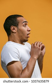 Doubt concept. Doubtful Afro-American man is looking frightenedly. Young emotional man. Human emotions, facial expression concept. Profile . Studio. Isolated on trendy orange