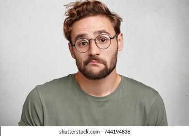 Doubt, expression and people concept. Uncertain bearded hipster guy shrugs shoulders, curves lips, doesn`t know answer, isolated over white background. Man feels indecisive about his future plans