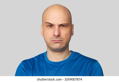 Doubt expression. Uncertain bald man curves lips and raised eyebrow. Isolated over gray background