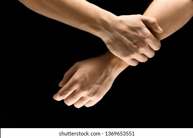Doubt and uncertainty. Male hands demonstrating a self holding gesture isolated on black studio background. Concept of human relations, relationship, phycology or business.