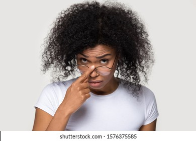 Doubtful African American woman taking off glasses, touching eyewear by finger, unsure young female feeling confused, looking at camera with disbelief, amazing news, isolated on studio background