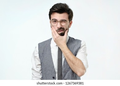 Doubtful bearded young spanish man looking with mistrust. Negative human emotion