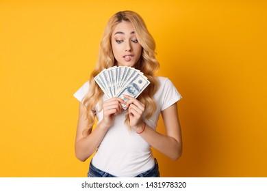 Doubtful Girl Holding Bunch Of Money Banknotes Over Yellow Studio Background