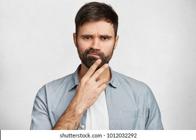 Doubtful hesitant displeased male curves lips, has gloomy expression, dark stubble, can`t decide or make choice, dressed in casual shirt, isolated over white background. Facial expressions concept